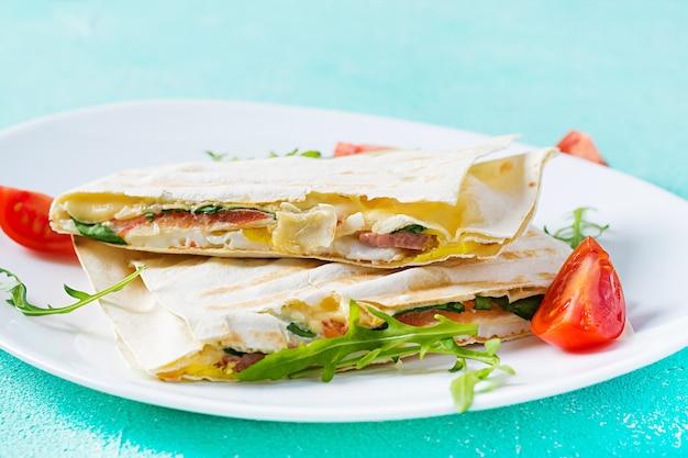 Domowy placek z szynką, jajkiem, serem i pomidorami oraz zielonymi ziołami. tradycyjne podpłomyki.