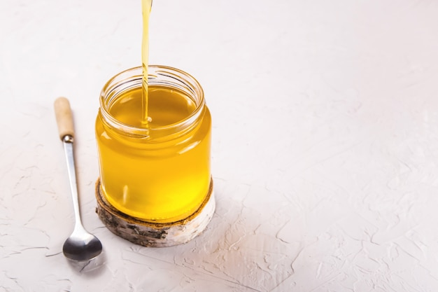 Domowy płynny ghee lub klarowane masło w przezroczystym słoju.