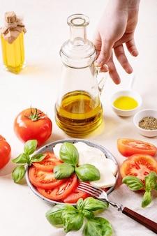 Domowy pomysł na zdrowy posiłek: pomidory koktajlowe, kulki mozzarelli, przyprawy, świeża bazylia i żeńska ręka trzymająca szklaną butelkę z oliwą z oliwek. sałatka mozzarella na białej powierzchni tekstury. skopiuj miejsce