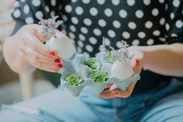 Domowy pomysł na złożenie z recyklingu wielkanocnego stroika z kwiatami i jajkami.