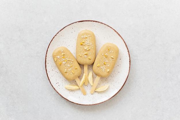 Domowy popsicle z czekoladowymi orzechami nerkowca na talerzu w formie kwiatów