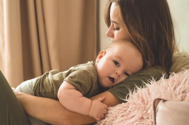 Domowy portret chłopiec z matką na łóżku. mama trzyma i całuje swoje dziecko. koncepcja dzień matki