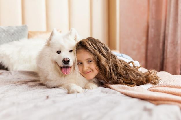 Domowy portret śliczny dziecka przytulenie z psem na kanapie