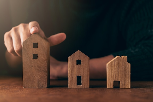 Domowy projekt decyzi pomysłów pojęcie z mężczyzna ręki wyboru domu kształta drewnianym modelem na brązu stole