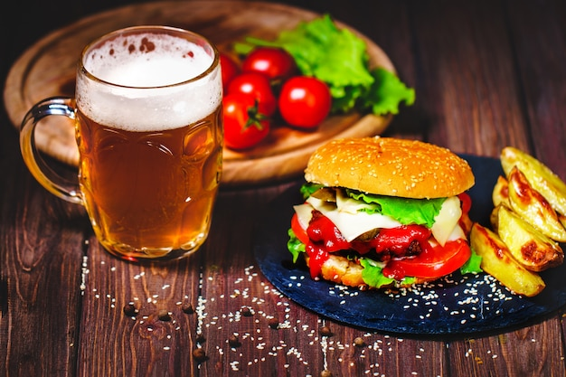 Domowy przepyszny, przepyszny burger wołowy z sałatą i ziemniakami, szklanka piwa podawana na kamiennej desce do krojenia. ciemny