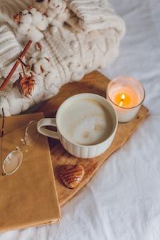Domowy przytulny wystrój. kubek cappuccino, ciasteczka, świeca na łóżku. zimowy poranek. jesień.