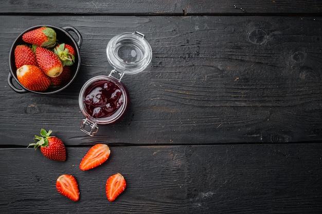 Domowy pyszny dżem truskawkowy i świeże jagody, na tle czarnego drewnianego stołu, płaski widok z góry z miejscem na tekst
