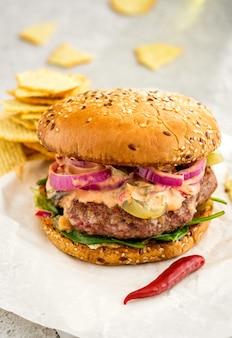 Domowy pyszny soczysty burger burgerowy z krążkami czerwonej cebuli, ogórkami kiszonymi i sosem.