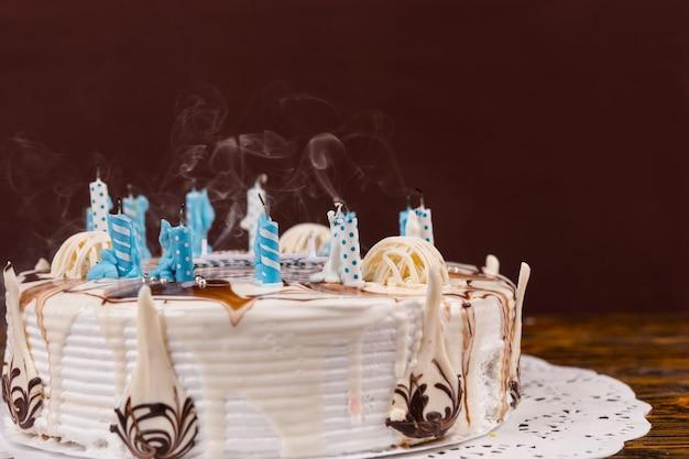 Domowy pyszny tort urodzinowy z mnóstwem zgaszonych świec na białej serwetce, na drewnianym biurku