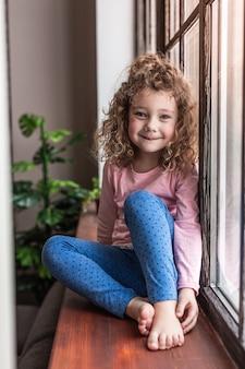 Domowy relaks. pozytywnie zachwycony dzieciak trzymający uśmiech na twarzy siedząc na parapecie