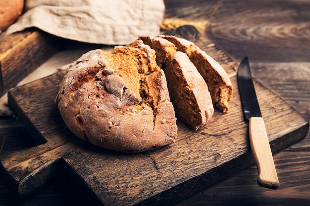 Domowy rustykalny chleb żytni z nasionami kolendry na drewnianej desce do krojenia.