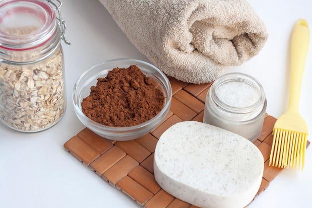 Domowy salon spa, gąbka, ręcznik, kawa, sól morska i płatki owsiane do robienia kosmetyków