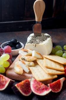 Domowy ser do smażenia halloumi z miętą na desce. tradycyjny ser grecki lub cypryjski na ciemnym tle z pomidorami, papryką, oliwkami, winogronami, figami i ziołami