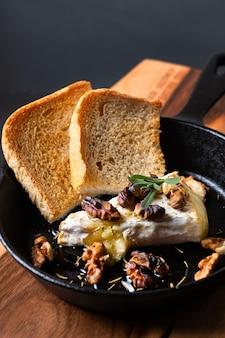 Domowy ser pieczony brie z miodem i orzechami włoskimi na patelni żelaznej