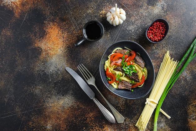 Domowy smażony wok z mięsem wołowym z widokiem z góry na tekst.