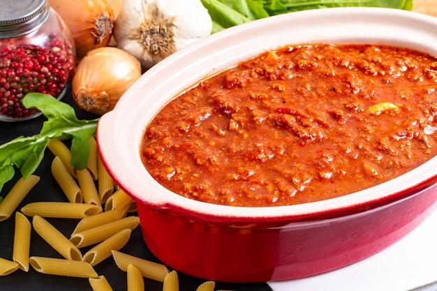 Domowy sos boloński o powolnym gotowaniu w czerwonym ceramicznym garnku i surowym penne