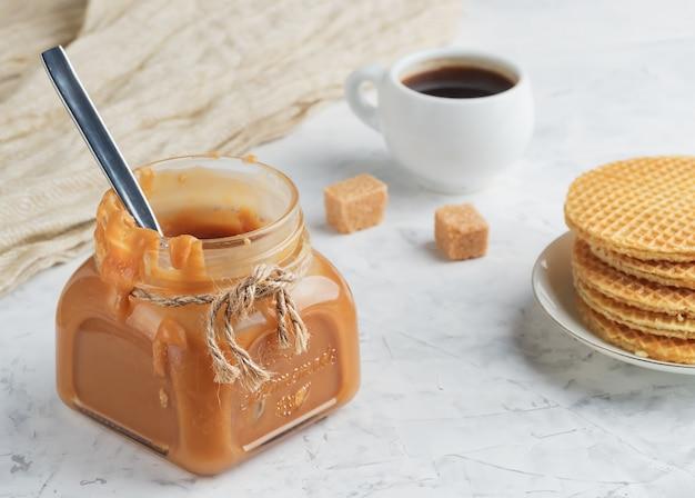 Domowy sos karmelowy w szklanym słoju na lekkim stole. espresso w białej filiżance i świeże gofry.
