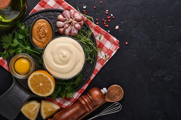 Domowy sos majonezowy i składniki cytryna, jajka, oliwa z oliwek, przyprawy i zioła, miejsce na czarnym tle. tło gotowania żywności. widok z góry.