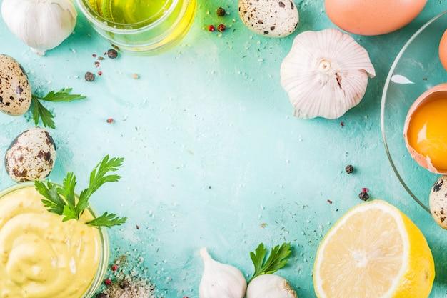 Domowy sos majonezowy ze składnikami - cytryną, jajkami, oliwą, przyprawami i ziołami, jasnoniebieski stół