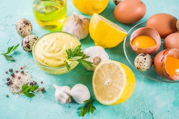 Domowy sos majonezowy ze składnikami - cytryną, jajkami, oliwą, przyprawami i ziołami