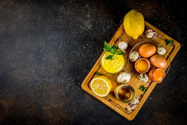 Domowy sos majonezowy ze składnikami - jajka z cytryny oliwa z oliwek przyprawy i zioła czarne tło betonowe domowy majonez ze składnikami