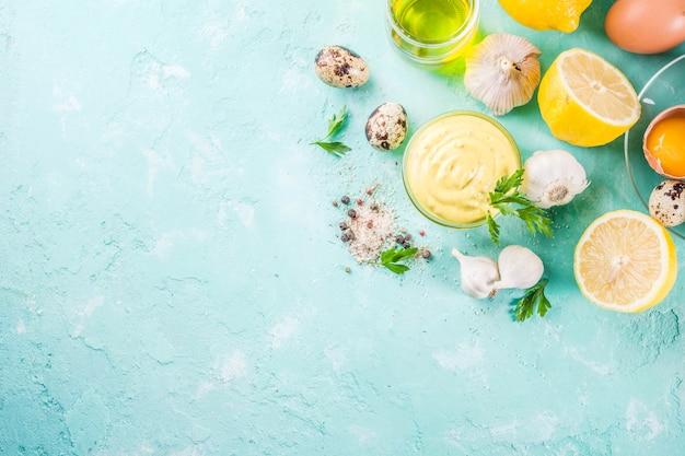 Domowy sos majonezowy ze składnikami - jajka z cytryny, oliwy z oliwek przyprawy i zioła jasnoniebieskie tło powyżej
