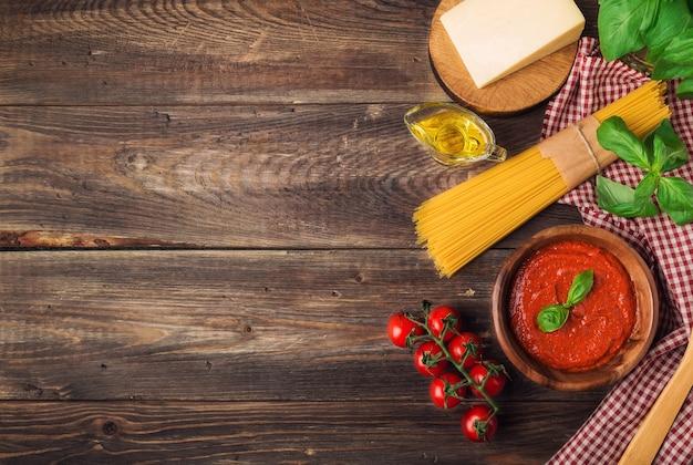 Domowy sos marinara, makaron spaghetti, parmezan, oliwa z oliwek, bazylia i pomidorki koktajlowe na rustykalnym drewnianym drewnie.