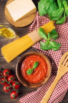 Domowy sos marinara, makaron spaghetti, parmezan, oliwa z oliwek, bazylia i pomidorki koktajlowe na rustykalnym drewnianym drewnie