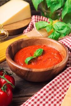 Domowy sos marinara, makaron spaghetti, parmezan, oliwa z oliwek, bazylia i pomidorki koktajlowe na rustykalnym drewnianym tle.