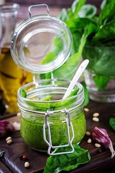 Domowy sos pesto świeża bazylia, orzeszki piniowe i czosnek na drewnianej powierzchni. włoskie jedzenie.
