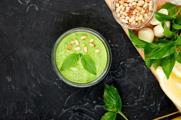 Domowy sos pesto w szklanym słoju ze składnikami.