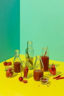 Domowy sos pomidorowy i oliwa z oliwek w szklanych butelkach na modnych żółtych świeżych pomidorach i wysokiej jakości zdjęciu papryki