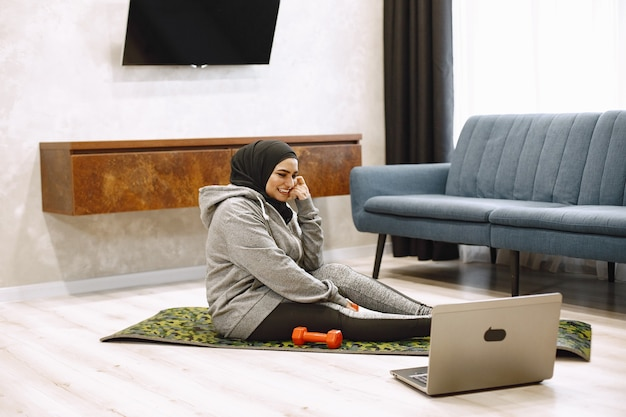 Domowy sport dla muzułmanek. uśmiechnięta arabska dziewczyna w hidżabie ćwiczy jogę online, ogląda samouczek wideo na laptopie, ćwiczy w salonie