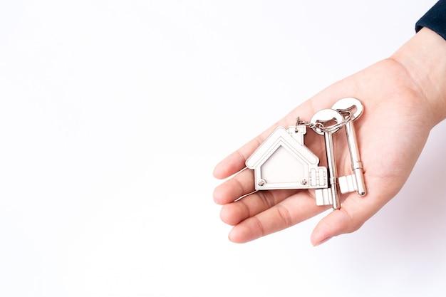 Domowy sprzedawca trzyma domowego klucz. koncepcja dla branży nieruchomości.