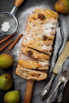 Domowy strudel gruszkowy, ozdobiony migdałami, anyżem i cukrem pudrem