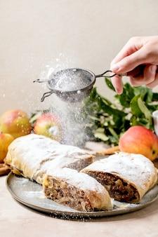 Domowy strudel jabłkowy pokrojony w plastry posypany cukrem pudrem z sitka w dłoni, na talerzu ceramicznym ze świeżymi jabłkami, zielonymi liśćmi i laskami cynamonu powyżej.