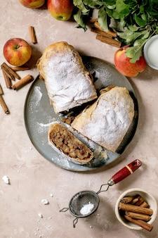 Domowy strudel jabłkowy pokrojony w plastry z cukrem pudrem na talerzu ceramicznym ze świeżymi jabłkami, zielonymi liśćmi i laskami cynamonu powyżej.