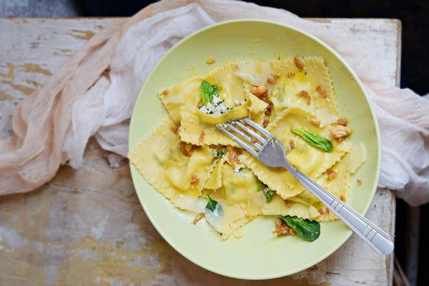 Domowy świeży makaron ravioli ze szpinakiem i serem ricotta, świeżą bazylią i czarnym pieprzem, parmezanem
