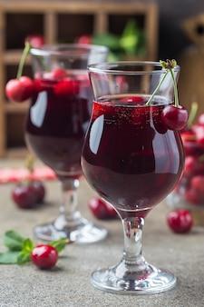 Domowy świeży sok wiśniowy w szklance ze świeżymi jagodami w stylu rustykalnym.
