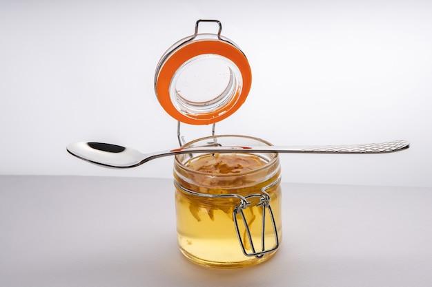 Domowy syrop z pigwy w szklanym słoiku z łyżeczką leżącą powyżej