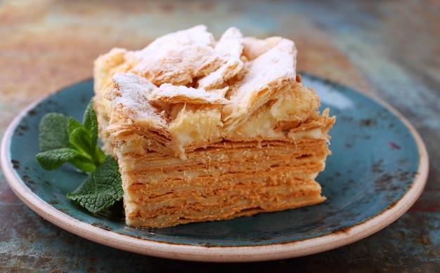 Domowy tort napoleoński przekładany kremem mlecznym ozdobiony miętą, na talerzu na rustykalnym tle.