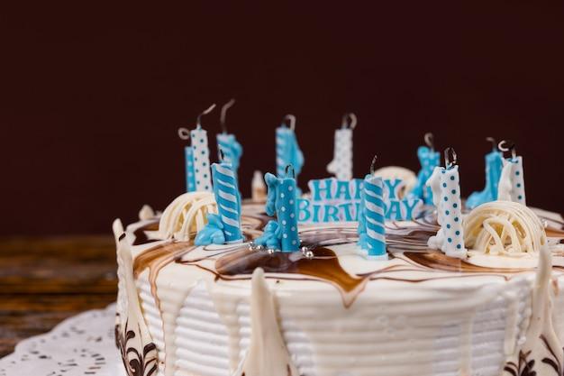 Domowy tort urodzinowy z mnóstwem zgaszonych świeczek na białej serwetce, na drewnianym biurku