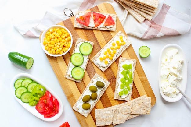 Domowy tost chrupiący z twarogiem i zielonymi oliwkami, plasterkami kapusty, pomidorów, kukurydzy, zielonego pieprzu na desce do krojenia. koncepcja zdrowej żywności, widok z góry. flat lay