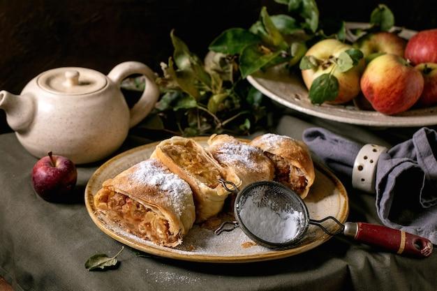 Domowy tradycyjny strudel jabłkowy w plasterkach w nakrapianym talerzu ceramicznym podawany z dojrzałymi świeżymi jabłkami, gałązkami, sitkiem i cukrem pudrem na ciemnym lnianym obrusie. jesienny nastrój picia herbaty.