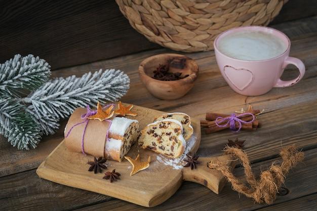 Domowy tradycyjny świąteczny stollen z suszonymi jagodami, orzechami i cukrem pudrem na blacie stoi na rustykalnym drewnianym stole z filiżanką kawy i gałęziami jodły