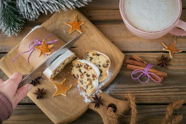Domowy tradycyjny świąteczny stollen z suszonymi jagodami, orzechami i cukrem pudrem na blacie stoi na rustykalnym drewnianym stole