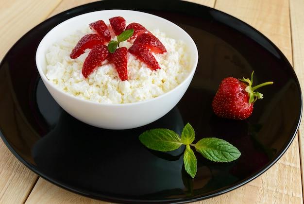 Domowy twarożek ze świeżymi truskawkami, dekoracja liści mięty w białej misce na czarnym naczyniu. przydatne śniadanie ekologiczne. zdrowe odżywianie.