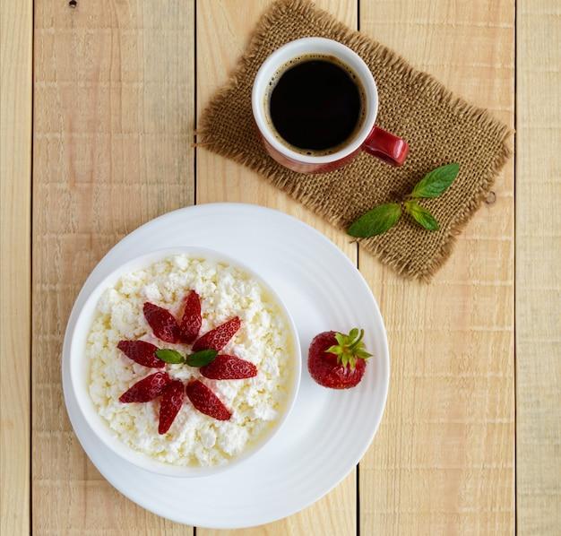 Domowy twarożek ze świeżymi truskawkami, miętą w białej misce i filiżanką kawy. przydatne śniadanie