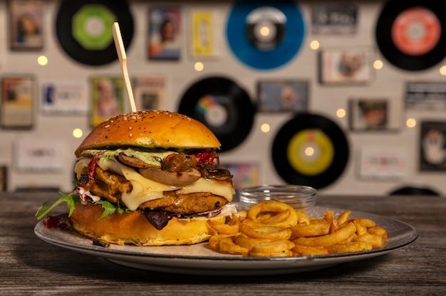 Domowy wegański hamburger z ciecierzycy, smażonych grzybów, sera emmenthal i frytek na drewnianym stole. odosobniony obraz.