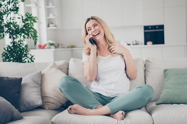 Domowy wesoły piękna dama siedzieć na kanapie trzymać telefon rozmawia